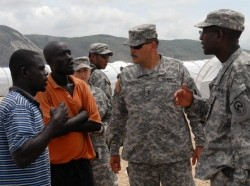 commander of JTF-Haiti asks a few Haitians about the living conditions at the internally displaced persons camp