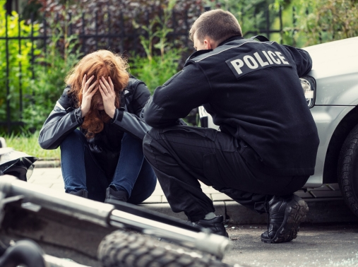 A policeman talks to a distressed person on the street