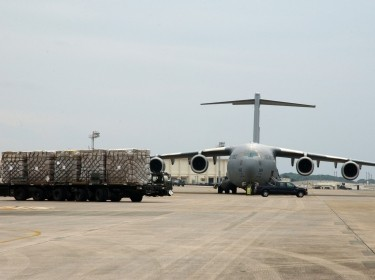 A C-17 from Elmendorf Air Force Base, Alaska, sits on the ramp here while food and cold weather supplies prepare to be loaded onto another C-17 (not pictured) from Hickam Air Force Base, Hawaii, Feb. 8., photo by Senior Airman Jeremy McGuffin/U.S. Air Force