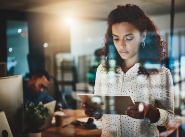 Shot of a young businesswoman using a digital tablet during a late night at work, photo by PeopleImages/Getty Images