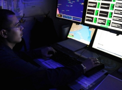 intelligence specialist monitors automatic identification systems aboard the aircraft carrier USS George H.W. Bush