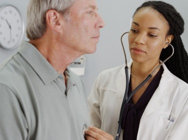 Doctor listening to an elderly man's heartbeat with a stethoscope, photo by rocketclips/Adobe Stock