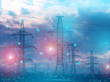 Electric power lines behind a network illustration, photo by kosssmosss/Adobe Stock