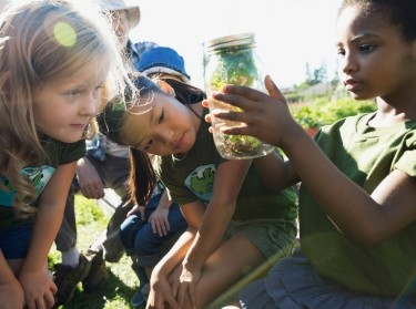 Girls looking at a plant jar in a garden