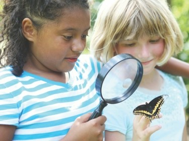 two girls observing a butterfly through a magnifying glass