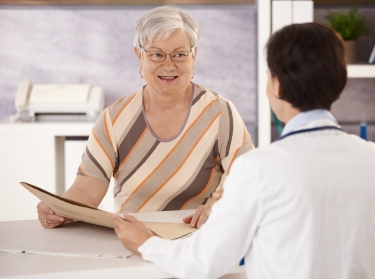 a middle aged woman checking out at a medical reception counter