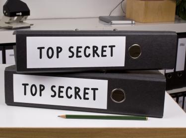 two binders marked top secret on a desk