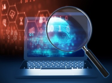A magnifying glass on a digital human hacker image, photo by monsitj/Getty Images