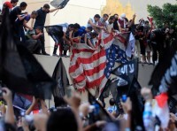 Protesters destroy an American flag pulled down from the U.S. embassy in Cairo September 11, 2012, photo by Mohamed Abd El Ghany/Reuters