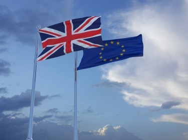 British and European Union flags in a cloudy sky, photo by themotioncloud/Getty Images