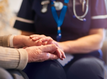 Close up of a nurse holding an elderly patient's hands, photo by MartinPrescott/Getty Images