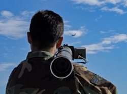 A soldier aims a portable anti-aircraft weapon at a target