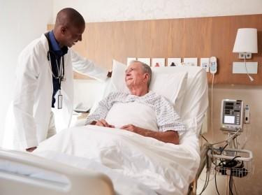 Doctor standing next to a hospital bed, talking to an elderly male patient, photo by monkeybusinessimages/Getty Images