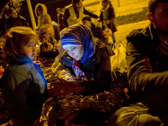 A refugee mother looks at her smartphone after arriving by rubber raft from Turkey to the Greek island of Lesbos near the port city of Mytilene, Greece, March 9, 2016, photo by Kay Nietfeld/Picture Alliance/dpa/AP Images
