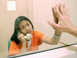 A woman taking a call in prison, photo by Thinkstock Images/Getty Images