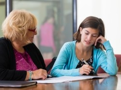 Student taking a placement test alongside a teacher, photo by SDI Productions/Getty Images