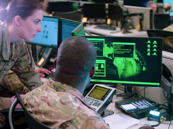 Capt. Sarah Miller and Tech. Sgt. Carrol Brewster discuss options in response to a staged cyber attack during filming of a scene for an AFRC mission video at Joint Base San Antonio-Lackland, Texas, June 1, 2019, photo by Maj. Christopher Vasquez/U.S. Air Force