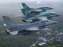 A U.S. Air Force F-16 Fighting Falcon fighter pilot flies alongside two Indonesian air force F-16 Fighting Falcon fighter pilots over the Sam Ratulangi International Airport in Manado, Indonesia