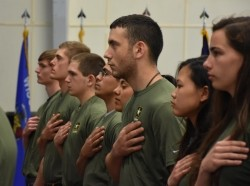 Graduating high school seniors who have committed to enlist in the Armed Forces following high school graduation stand as the National Anthem plays during an Our Community Salutes event at Fort McCoy, Wisconsin on Armed Forces Day, May 20, 2017, photo by Ted Small/Alamy Stock Photo
