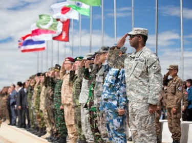 Service members from participating nations salute during the opening ceremony of Khaan Quest 2014, a multinational exercise designed to promote regional peace and security. It is