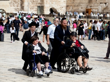 Men assisting women in wheelchairs at at the Western Wall, Jerusalem, Israel