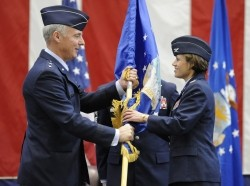Maj. Gen. Winfield Scott III, 18th Air Force commander, passes the wing flag to Col. Gina Grosso, the new 87th Air Base Wing commander, during an assumption of command ceremony here March 3. Colonel Grosso will be the first joint base commander of JB McGuire-Dix-Lakehurst