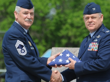 Col. Wobbema presents a flag to Chief Master Sgt. Clemenson during his retirement ceremony at the North Dakota Air National Guard, Fargo, N.D.