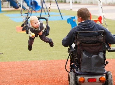 Father in wheelchair with child on swing