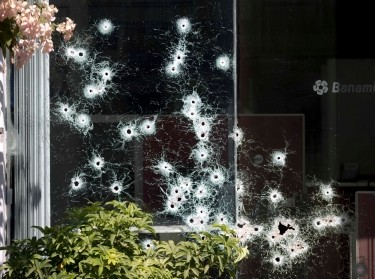 The window of a bank is riddled with bullet holes in the town of Apatzingan, Michoacan state, Mexico