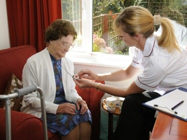 Healthcare visitor helping an elderly lady with a panic alarm fob