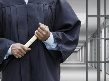 prisoner graduating holding a diploma