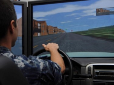 Intelligence Specialist Seaman drives a simulator during the Save a Life Tour