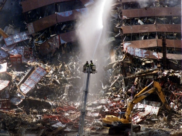 New York City firefighters pour water on the wreckage of 7 World Trade Cente