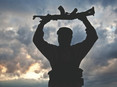 silhouette of militant with rifle