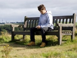 Man on a bench in countryside using mobile