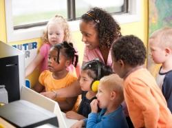 A kindergarten teacher with children at the computer