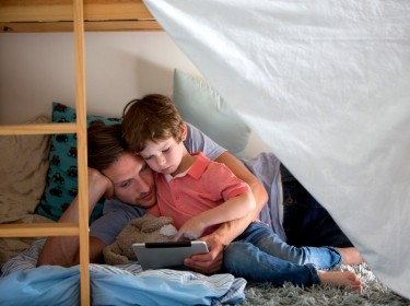 Father and son using an electronic tablet on bunk beds