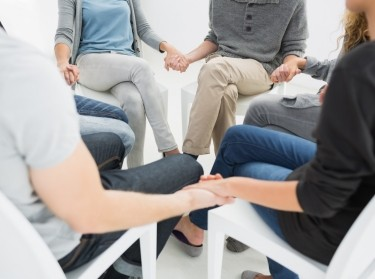 Group of people holding hands in counseling session