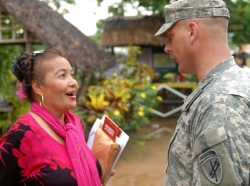 A service member talks with a local official during outreach activities in the Philippines