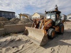 A bulldozer is parked in the Queens borough of New York where a concrete foundation is all that remains of a house that burned to the ground during Superstorm Sandy in October 2012