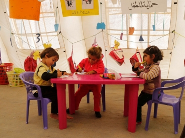 Syrian refugee children draw inside a makeshift school, supported by UNICEF and in cooperat