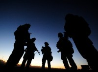 A silhouette of service members standing in a circle