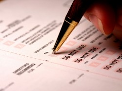 A voter fills out an absentee ballot