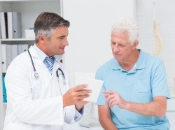 A doctor explains medication to an older male patient