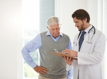 Male doctor looking at a clipboard while talking to an elderly male patient