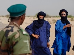 A Malian soldier speaks with Tuareg men in the village of Tashek, outside Timbuktu, July 27, 2013