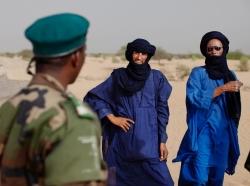 A Malian soldier speaks with Tuareg men in the village of Tashek, outside Timbuktu, July 27, 2013