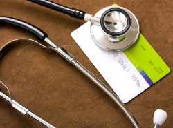 A stethoscope rests on a credit card.