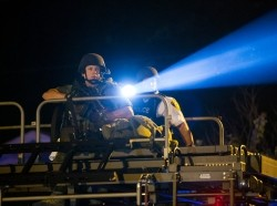 A police officer points a spotlight at a group of demonstrators near Ferguson, Missouri in August 2014