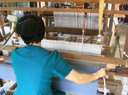 Worker weaving fabric on loom in factory